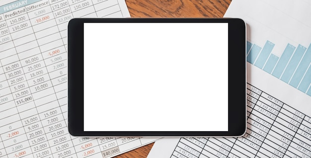 Tablet z pustym tłem na pulpicie z dokumentami, raportami i wykresami. koncepcja biznesowa i finansowa