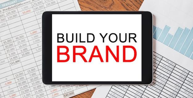 Tablet z tekstem buduj swoją markę na swoim pulpicie za pomocą dokumentów. koncepcja biznesu i finansów
