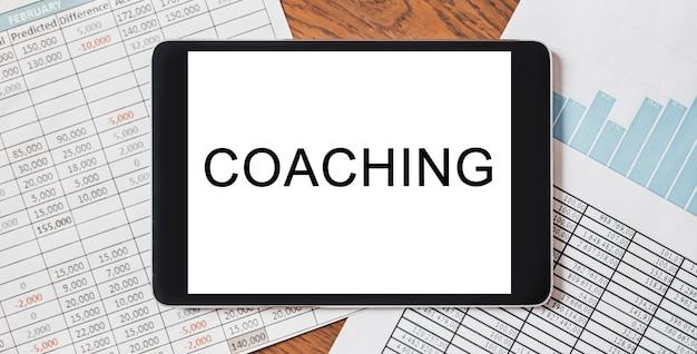 Tablet z tekstem coaching na twoim pulpicie z dokumentami, raportami i wykresami. koncepcja biznesu i finansów
