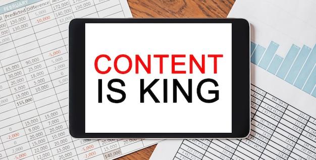 Tablet z tekstem content is king na pulpicie z dokumentami, raportami i wykresami