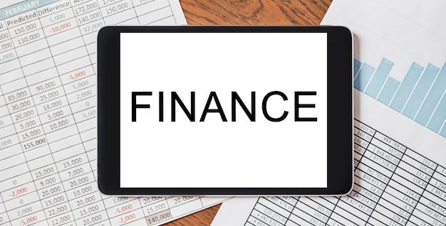 Tablet z tekstem finance na pulpicie z dokumentami, raportami i wykresami