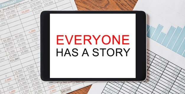 Tablet z tekstem każdy ma historię na pulpicie. koncepcja biznesu i finansów