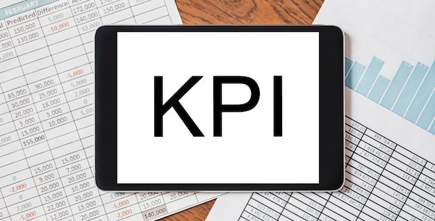 Tablet z tekstem kpi na pulpicie z dokumentami, raportami, wykresami. koncepcja biznesu i finansów