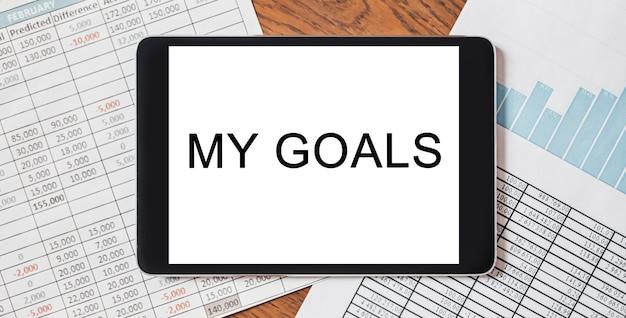 Tablet z tekstem moje cele na pulpicie z dokumentami, raportami i wykresami. koncepcja biznesu i finansów