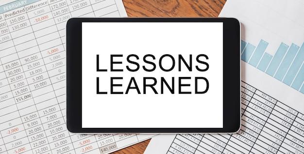 Tablet z tekstem nauczone lekcje na pulpicie z dokumentami, raportami i wykresami. koncepcja biznesu i finansów