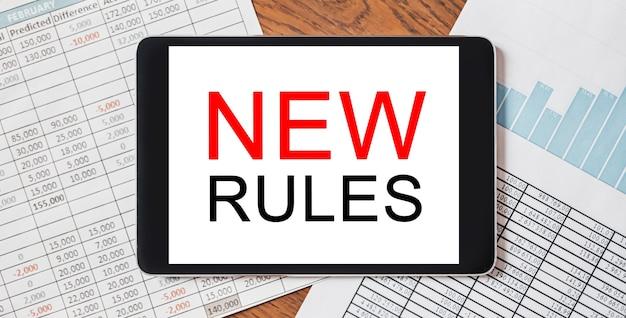Tablet z tekstem nowe reguły na pulpicie z dokumentami, raportami i wykresami. koncepcja biznesu i finansów