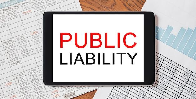Tablet z tekstem odpowiedzialność publiczna na twoim pulpicie z dokumentami, raportami i wykresami. koncepcja biznesu i finansów