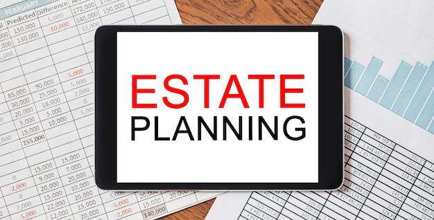 Tablet z tekstem planowanie nieruchomości na pulpicie z dokumentami. koncepcja biznesu i finansów