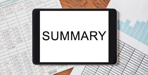 Tablet z tekstem podsumowanie na pulpicie z dokumentami, raportami i wykresami. koncepcja biznesu i finansów