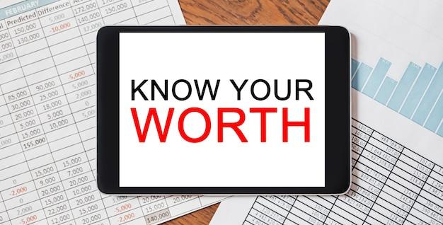 Tablet z tekstem poznaj swoją wartość na pulpicie z dokumentami. koncepcja biznesu i finansów