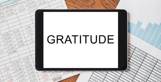 Tablet z tekstem wdzięczność na pulpicie z dokumentami, raportami i wykresami. koncepcja biznesu i finansów