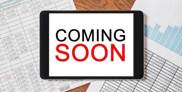 Tablet z tekstem wkrótce na pulpicie z dokumentami. koncepcja biznesu i finansów