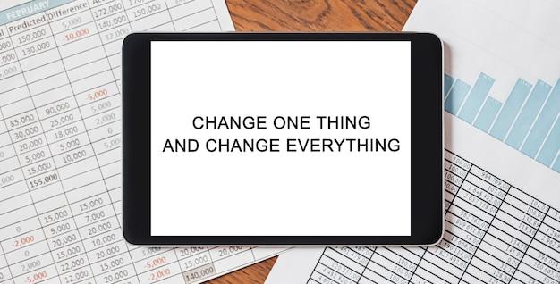 Tablet z tekstem zmień jedną rzecz i zmień wszystko na pulpicie za pomocą dokumentów, raportów i wykresów