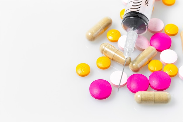 Tabletka leku i strzykawka