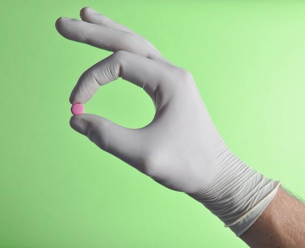 Tabletka pigułkowa w dłoni z lateksowymi rękawiczkami
