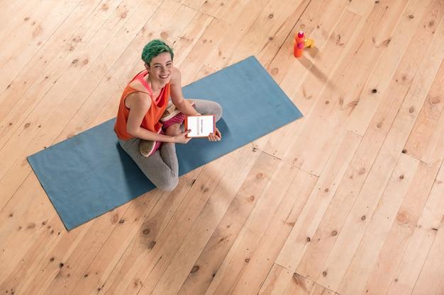 Tabletka po ćwiczeniach. zajęta piękna zielonowłosa freelancerka używająca pomarańczowej tabletki po porannych ćwiczeniach