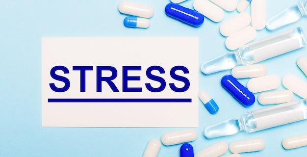 Tabletki, ampułki i biała kartka z napisem stres na jasnoniebieskim tle. koncepcja medyczna