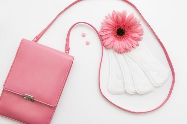 Tabletki antykoncepcyjne, białe miękkie podpaski na dzień i kwiatek z żeńską różową torebką, leżący na płasko. zdrowie kobiety, koncepcja równowagi hormonalnej