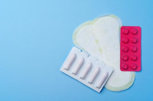 Tabletki antykoncepcyjne, podpaski higieniczne i tampony na niebieskim tle