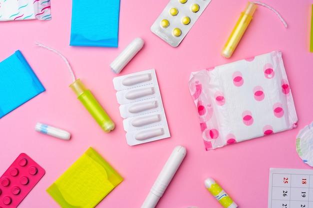 Tabletki antykoncepcyjne, podpaski higieniczne i tampony na różowym tle, widok z góry