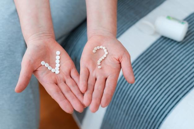 Tabletki i pigułki w rękach kobiety w formie znaku zapytania i symbolu vivat. pytanie i wątpliwości dotyczące przyjmowania leków.