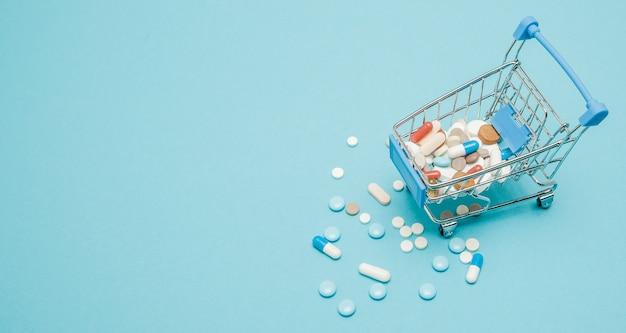 Tabletki i wózek na zakupy. kreatywny pomysł na koszt opieki zdrowotnej, aptekę, ubezpieczenie zdrowotne i koncepcję biznesową firmy farmaceutycznej. skopiuj miejsce