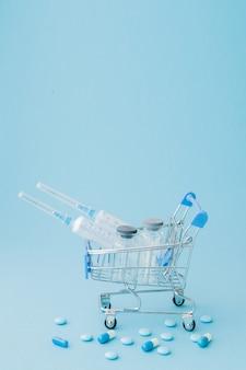 Tabletki i zastrzyki medyczne w wózku na zakupy. kreatywny pomysł na koszt opieki zdrowotnej, aptekę, ubezpieczenie zdrowotne i koncepcję biznesową firmy farmaceutycznej. skopiuj miejsce