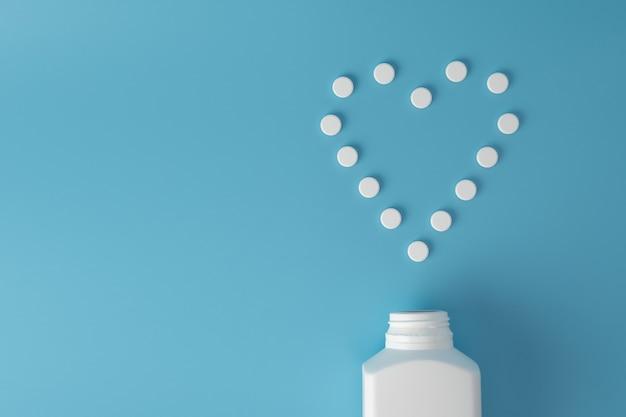 Tabletki leku w kształcie serca na niebieskiej powierzchni