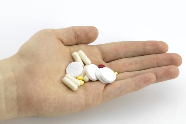 Tabletki lub kapsułki leku w dłoni, dłoni lub palcach lekarza lub pielęgniarki. recepta na leki lecznicze. lek farmaceutyczny, lekarstwo w pojemniku na zdrowie. antybiotyk