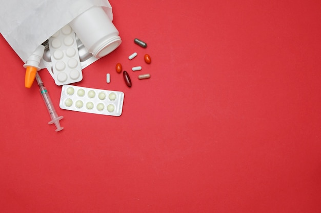 Tabletki medycyny na czerwonym tle, miejsca na tekst. koncepcja apteki medycyny