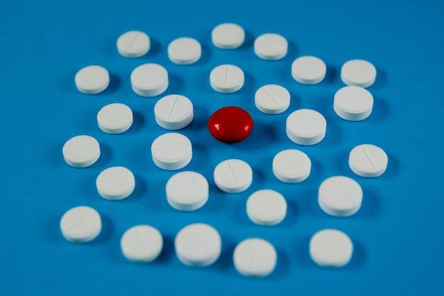 Tabletki medyczne i zdrowotne na niebieskim tle widok z boku