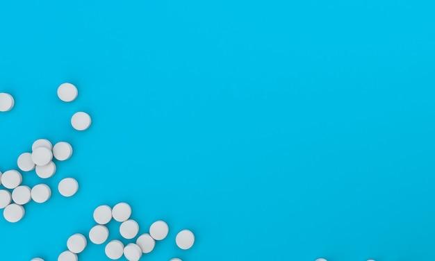Tabletki medyczne rozrzucone na jasnoniebieskim tle