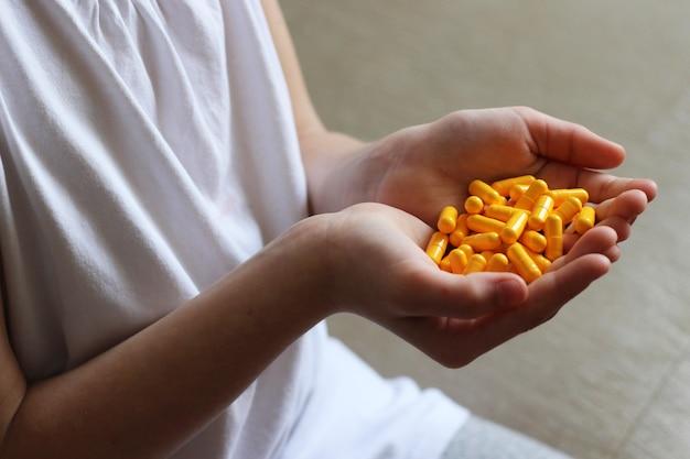 Tabletki medyczne w rękach dziecka z bliska