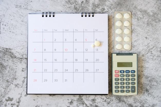 Tabletki na tle kalendarza. koncepcja opieki zdrowotnej