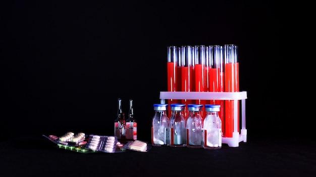 Tabletki na tle probówek z czerwonym płynem i ampułki na czarnym tle.