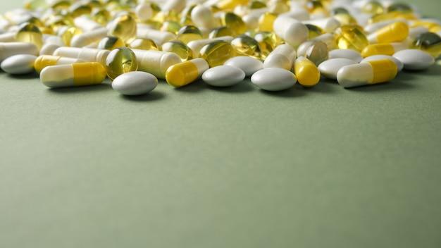Tabletki są porozrzucane na stole. tabletki na zielonym tle. tabletki lecznicze, kapsułki.