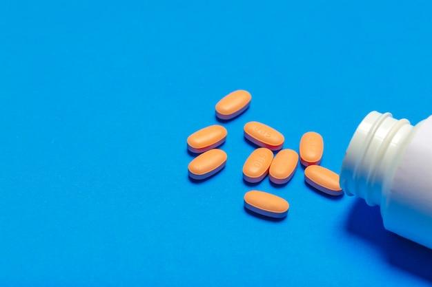 Tabletki są rozrzucone na niebieskim tle
