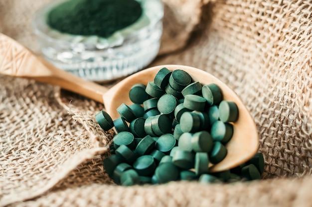 Tabletki spiruliny z wodorostów, chlorelli na drewnianej łyżce z bliska. super jedzenie wegetariańskie z białkiem roślinnym