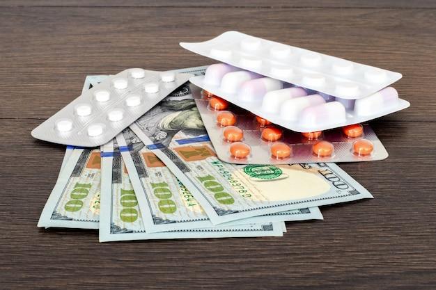 Tabletki w blistrach i pieniądze na drewnianym stole