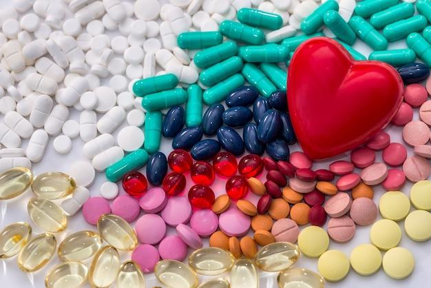 Tabletki w kolorach tęczy z czerwonym sercem