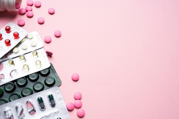 Tabletki w opakowaniach farmaceutyki widok z góry różowe tło lekarstwo