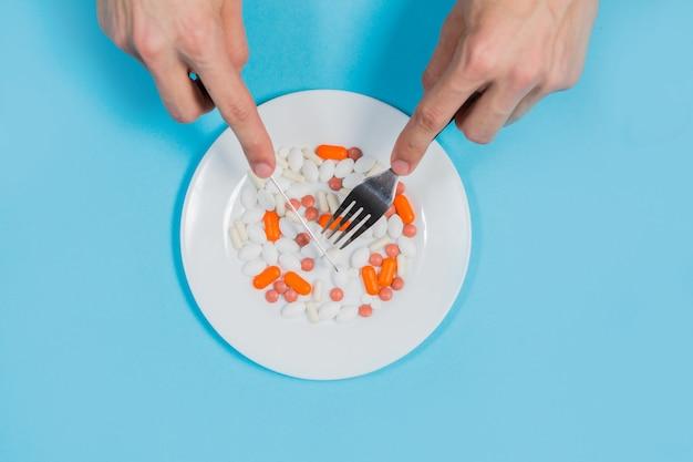 Tabletki w talerzu z widelcem i nożem
