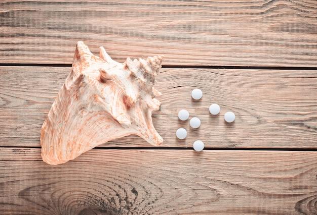 Tabletki wapnia i muszli na drewnianym stole. pojęcie medyczne. minerały dla zdrowia. widok z góry.