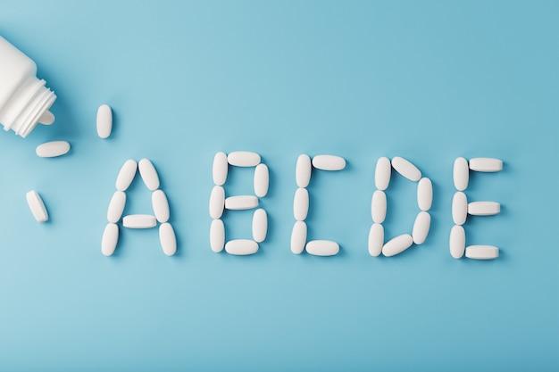Tabletki witaminy abcde wypadły z białego słoika na niebieskim tle. litera abcde to napis. pojęcie ochrony immunologicznej, profilaktyka przeciwwirusowa. dodatki do żywności. wolna przestrzeń