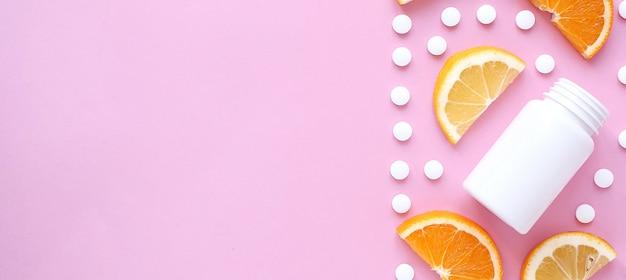Tabletki witaminy i butelkę z cytryną pomarańczowy na różowym tle
