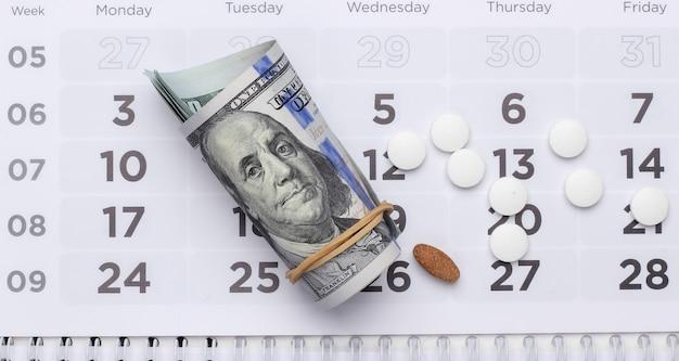 Tabletki z dolarowymi w kalendarzu. koncepcja opieki zdrowotnej i medycyny