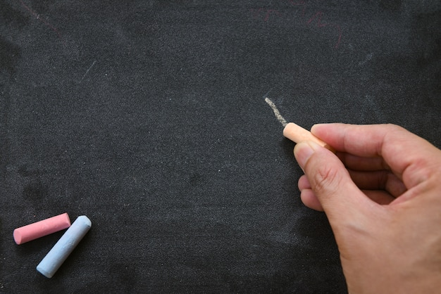 Tablica ciemna lub tablica z kredą poziomą i baner / tablica tekstury w ręku pisze i rysuje dla edukacji w szkolnej tablicy