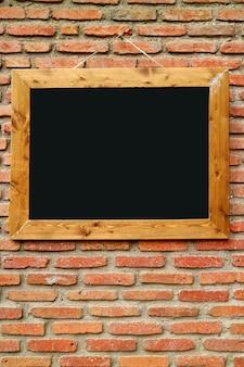 Tablica drewniana rama na tle retro ceglany mur