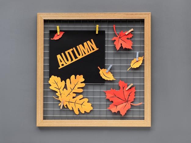 """Tablica fotograficzna z czerwonym i pomarańczowym papierem jesienne liście i tekst """"jesień"""". upadek papierowego rękodzieła do projektowania wnętrz lub kreatywnych pomysłów na dekorację domu."""