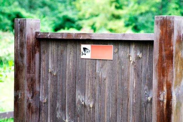 Tablica informacyjna wykonana z drewna w parku, z ikoną monitoringu.
